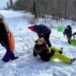 Klouzající se děti na sněhu.